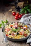 Italian fusilli spiral pasta. With grape tomatoes, olives, prosciutto and parmigiano cheese on a plate royalty free stock image