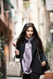 Italian Girl. A young beautiful dark hair woman with a handbag walking with intent in the beautiful narrow streets of Genoa, an old Italian harbor city Stock Images