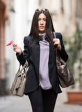 Italian Girl. A young beautiful dark hair woman with a handbag walking with intent in the beautiful narrow streets of Genoa, an old Italian harbor city stock photography