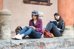Italian girls are relaxing sitting reading a book Stock Images