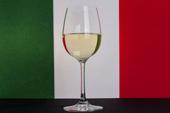 Italian glass of wine center. The photo shows the glass of wine on the background of the Italian flag Royalty Free Stock Image