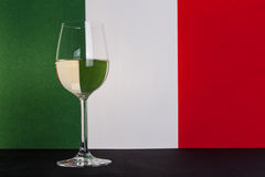 Italian glass of wine left. The photo shows the glass of wine on the background of the Italian flag Stock Photography