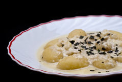 Italian gnocchi with four cheese sauce isolated on black Stock Photo