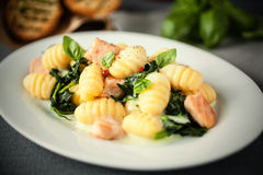 Italian gnocchi pasta with salmon and fresh basil Stock Image