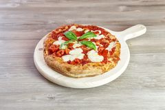 Italian gourmet pizza on wooden chopping board. Focaccia with tomato sauce, basil and mozzarella Stock Photo