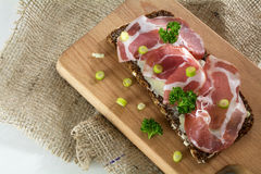 Italian ham coppa or capicola on dark bread on a wooden cutting Stock Image