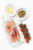 Italian ham prosciutto bread sticks with olive oil and tomatoes Royalty Free Stock Images