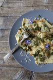 Italian handmade pasta ravioli with borage herb, flower, sage, crisp onion Royalty Free Stock Photos