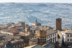 An Italian hilltop town sits high above the countryside in the distance. royalty free stock photography