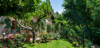 Italian home and garden on sunny day outisde. Beautiful flowering garden and cottage Royalty Free Stock Photo