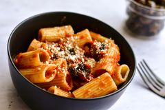 Pasta alla puttanesca. Italian home made sedani alla puttanesca Olives and tomato sauce royalty free stock photography