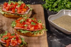 Italian homemade bruschetta with chopped tomatoes, salad leaves, ham and sauce on grilled crusty bread. horizontal view stock photos