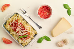 Italian homemade pasta with tomato sauce, basil and parmesan che. Top down view of homemade italian fusilli pasta with pelati tomato sauce, fresh green basil Royalty Free Stock Images