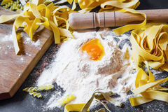 Italian homemade pasta with wheat flour and egg on black backgro Stock Image