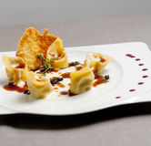 Italian homemade ravioli with cheese in a white plate. Yellow royalty free stock photo