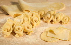 Italian homemade tortellini and raw handmade dough,placed on  wooden table and sprinkled with flour. Stock Photos