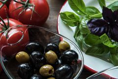 Italian ingredients top view. Top view of basil, tomatoes, olive on wooden background royalty free stock photos