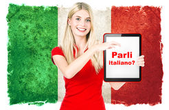 Italian language learning concept. Parli italiano? italian language learning concept. young woman with italian national flag on the background holding tablet pc Royalty Free Stock Photos