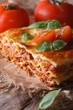 Italian lasagna with basil close-up on paper, vertical rustic Royalty Free Stock Photography