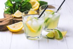 Italian lemon lime liqueur limoncello with ice and mint. Tradtitional Italian homemade lemon and lime liqueur limoncello with ice and mint on wooden background Royalty Free Stock Images