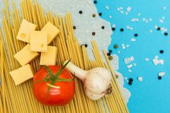 Italian macaroni ingredients on a blue background, top view, copy space.  royalty free stock image