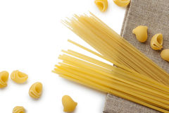 Italian macaroni shells and spaghetti with rope on brown bagging Royalty Free Stock Images