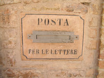 Italian mailbox. An old Italian metal mailbox with the letters POSTA PER LE LETTERE on a vintage brick wall outdoors Royalty Free Stock Images