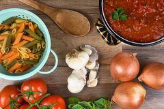 Italian Meal Ingredients. On a wood kitchen table. A pot of sauce, colander of rigatoni, tomatoes, garlic, oregano, and onions seen from a high angle Royalty Free Stock Image
