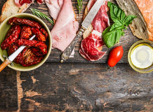 Italian meat plate with bread and antipasti on rustic wooden background, top view Royalty Free Stock Photos