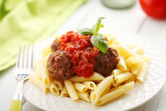 Italian meatballs with penne pasta in tomato sauce Stock Images
