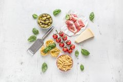 Italian or mediterranean food cuisine and ingredients on white concrete table. Tagliatelle pene pasta olives olive oil tomatoes. Italian or mediterranean food Royalty Free Stock Photography