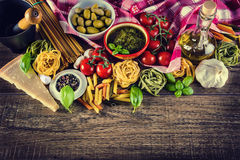 Italian and Mediterranean food ingredients on old wooden background. Spaghetti olives basil tomato pesto pasta garlic pepper olive oil and mortar Royalty Free Stock Photos