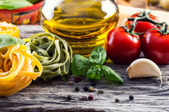 Italian and Mediterranean food ingredients on old wooden background. Spaghetti olives basil tomato pesto pasta garlic pepper olive oil and mortar Royalty Free Stock Photo
