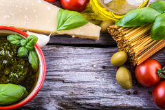 Italian and Mediterranean food ingredients on old wooden background. Spaghetti olives basil tomato pesto pasta garlic pepper olive oil and mortar Stock Photo