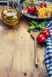 Italian and Mediterranean food ingredients on wooden background.Cherry tomatoes pasta, basil leaves and carafe with olive oil. Royalty Free Stock Image