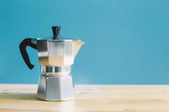 Italian metallic coffee maker Mocha coffee pot on wooden table Stock Images