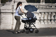 Italian mother and baby in a pram. An Italian mother carrying her baby in a pram. Italian mothers are known to be very affectionate towards their children Stock Photo