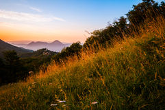 Italian mountain landscape with field of grass at sunset Stock Photos