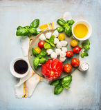 Italian mozarella tomatoes salad, ingrediets with oil and  balsamic vinegar on rustic wooden background Stock Photography