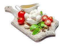 Italian mozzarella cheese and tomatoes. Caprese salad ingridients. Italian mozzarella cheese and tomatoes isolated on white background. Caprese salad ingridients Royalty Free Stock Image