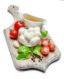 Italian mozzarella cheese and tomatoes. Caprese salad ingridients. Italian mozzarella cheese and tomatoes isolated on white background. Caprese salad ingridients Stock Photography