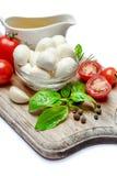 Italian mozzarella cheese and tomatoes. Caprese salad ingridients. Italian mozzarella cheese and tomatoes isolated on white background. Caprese salad ingridients Stock Photo