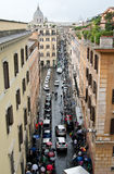 Italian narrow street leading to St. Peter's Basilica. On the street a lot of cars and people under umbrellas. Stock Image