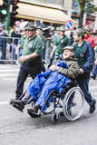 Italian old alpine military man with handicap helped by companies. Italian alpine military parade of Pordenone, may 2014: the platoon walks in the street while Royalty Free Stock Photo
