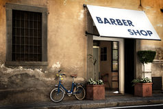 Italian old style bicycle. An italian old style small bike leaning against a wall outside an italian barber shop Stock Photos