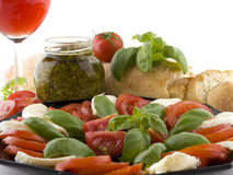 The italian party. Pesto a plate of tomatoes mozzerella and a glass of wine Royalty Free Stock Photos