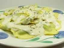 Italian pasta. Fresh italian pasta called mezzelune whit cheese sauce royalty free stock photography