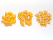 Italian pasta. Three different kinds of Italian pasta (conchiglie, creste di gallo, farfalle) against white background Stock Photos