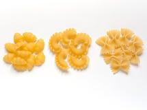 Italian pasta. Three different kinds of Italian pasta (conchiglie, creste di gallo, farfalle) against white background stock photos