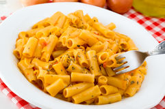 Italian pasta. A white plate with Italian pasta with spices and tomato sauce Royalty Free Stock Photo